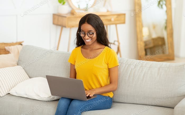 Portrait of young black lady using laptop computer for work or education on couch at home