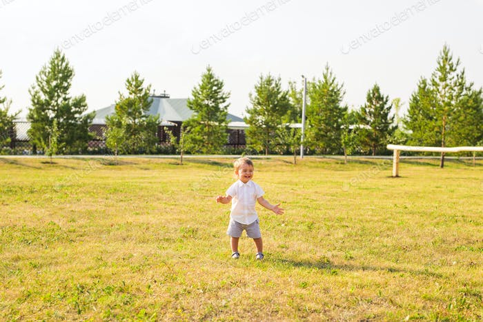 Portrait of cute little baby boy having fun outside. Smiling happy child playing outdoors