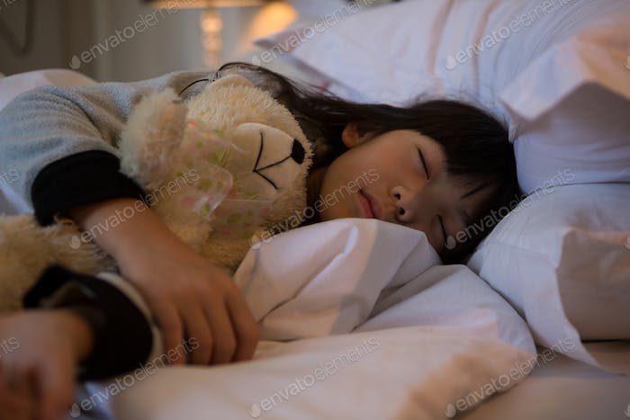 Girl with toy sleeping on bed at home