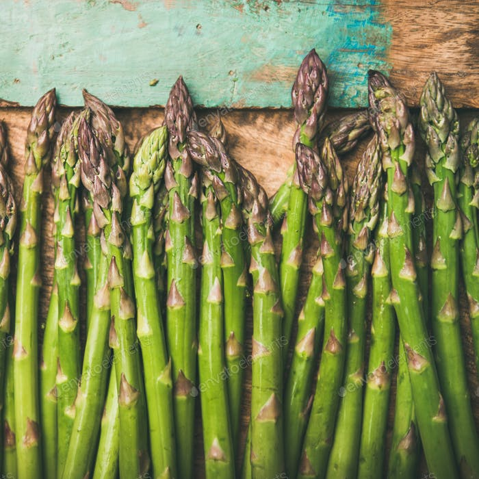 Raw uncooked green asparagus over rustic wooden tray background, square crop