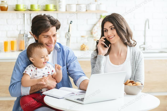 Millennial parents with baby son working on laptop at kitchen