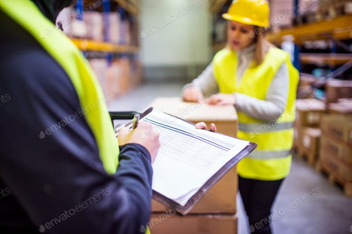 Young warehouse workers working together.