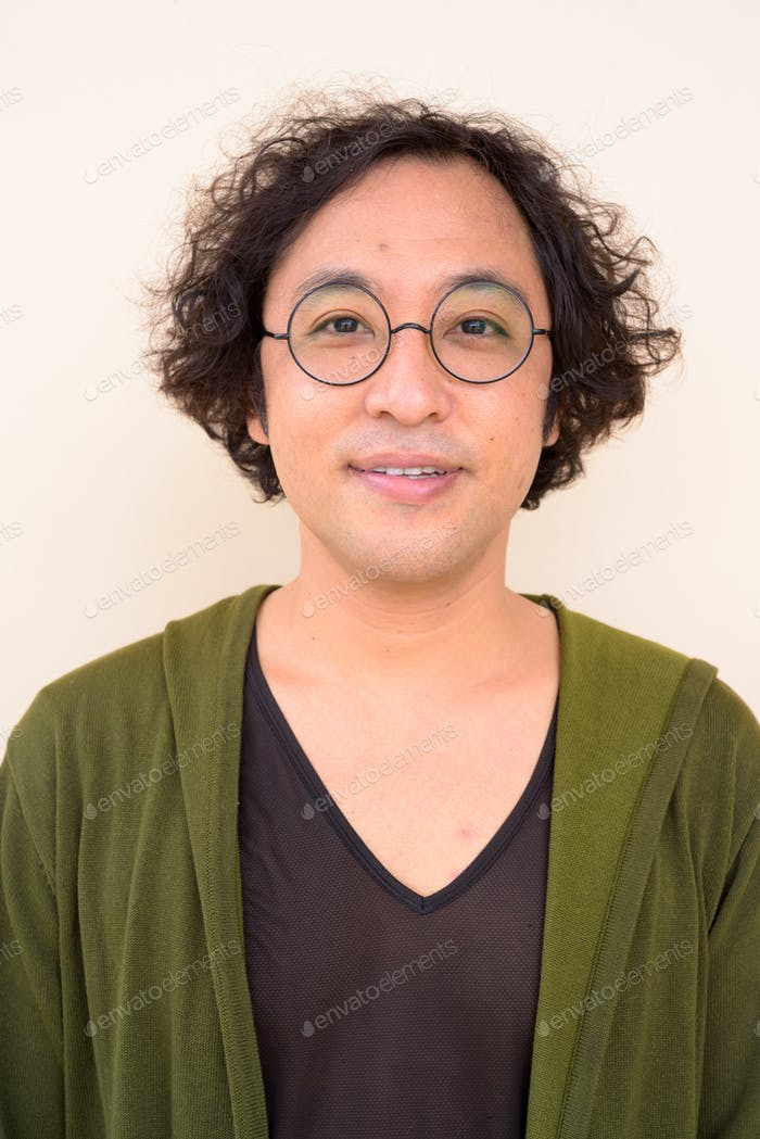 Face of Japanese man with curly hair wearing eyeglasses