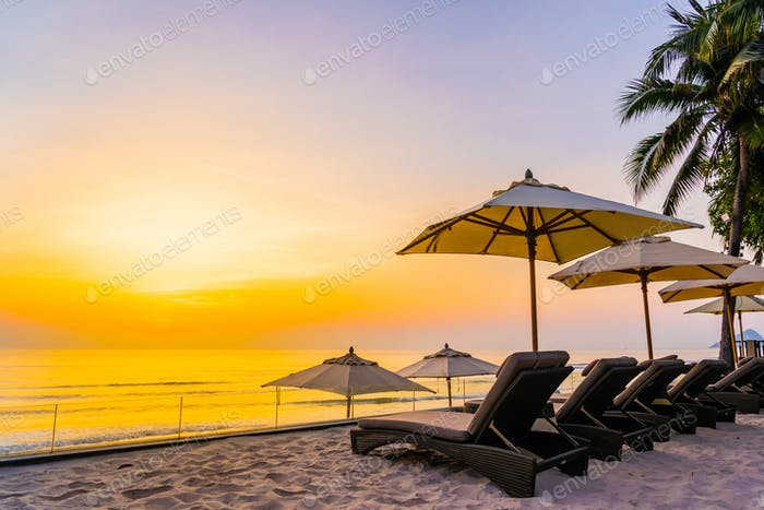 Umbrella and chair on the beautiful beach and sea at sunrise tim