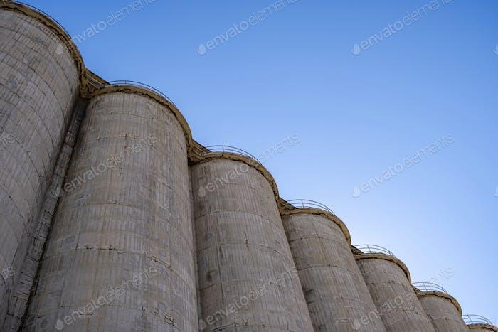 Large concrete industrial silos against blue sky background