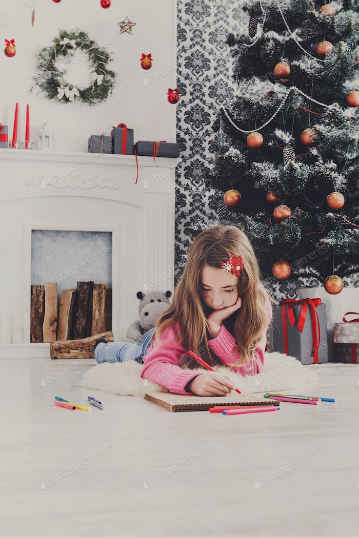 Beautiful girl writing letter to santa, wait for christmas