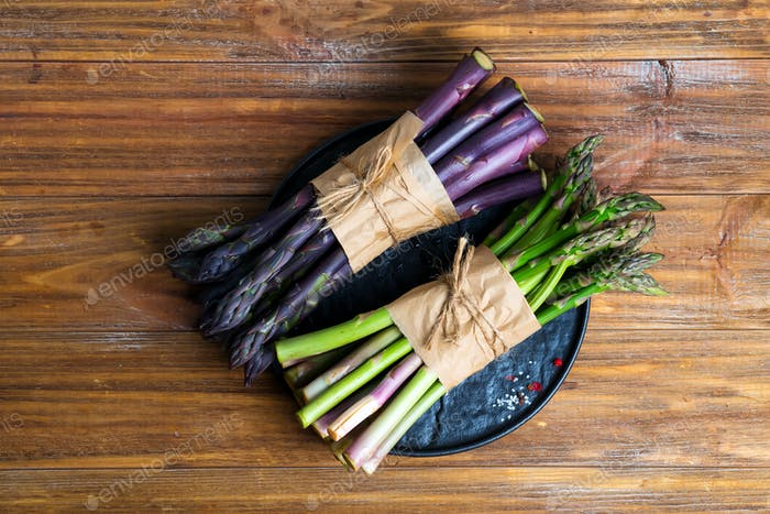Fresh natural organic two bundles of green and purple asparagus vegetables on a wooden background