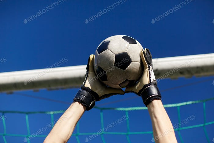 goalkeeper with ball at football goal over sky