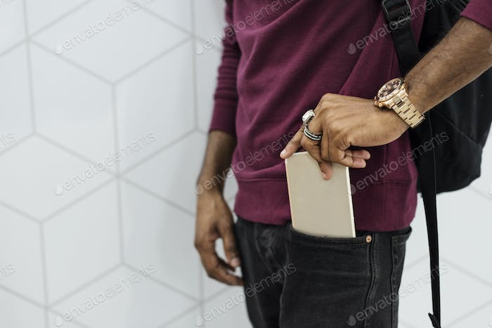 African man putting mobile phone on his pocket