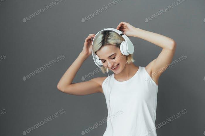 Cute girl in headphones over gray wall