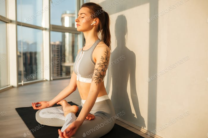 Lady in sporty top and leggings in lotus pose meditating listening music over beautiful view