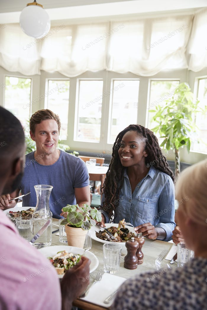 Group Of Friends Sitting At Table In Restaurant Enjoying Meal Together