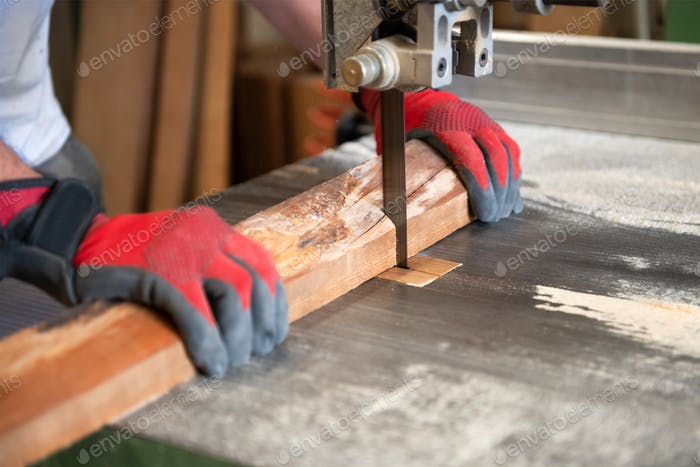 Carpenter cutting wood on a band saw