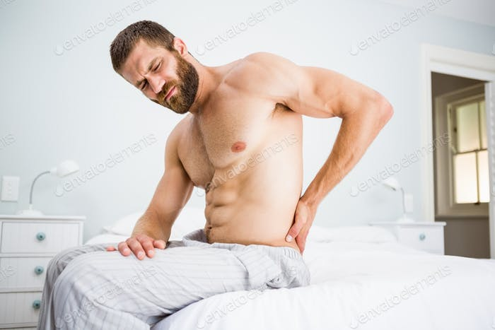 Man suffering from back pain on bed