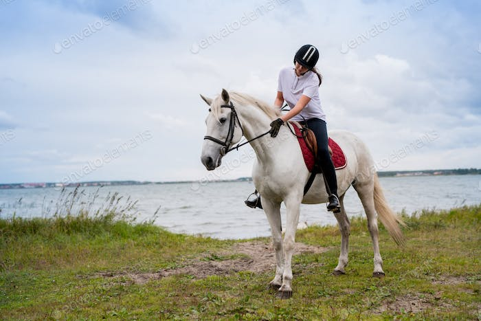 Active woman in equestrian outfit moving along river on back of white racehorse