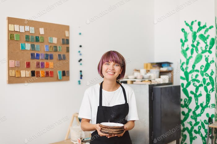 Cute smiling girl in black apron and white T-shirt holding handmade plates in hands