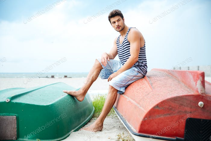 Handsome young man sitting on a fishing boat by sea