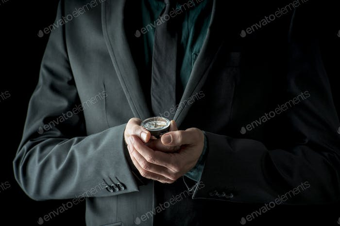 Businessman in suit holding compass in his hands