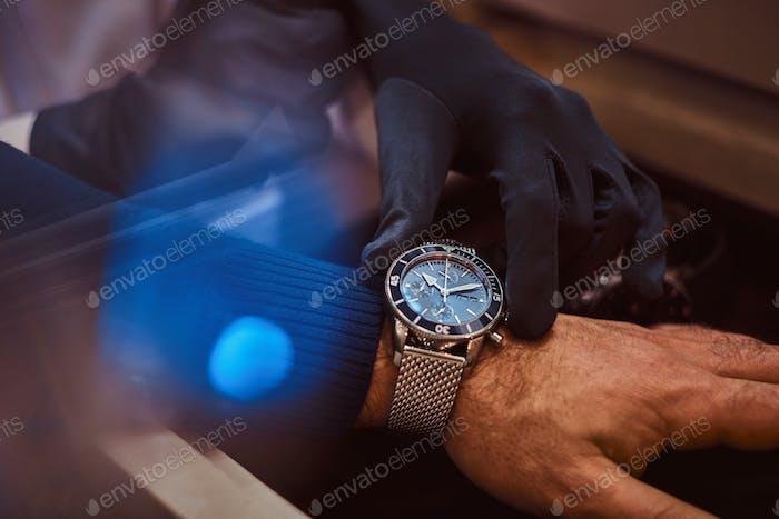 Assistant hilft dem Kunden, exklusive Herrenuhren, Nahzeiger anzuprobieren.