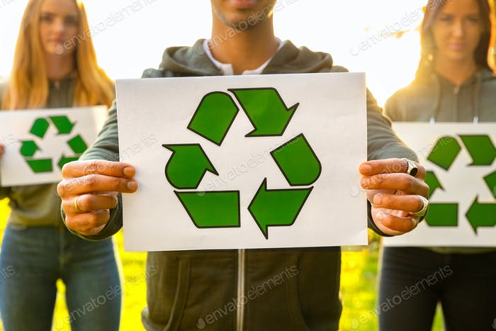Young volunteers holding recycling symbol placard outdoor