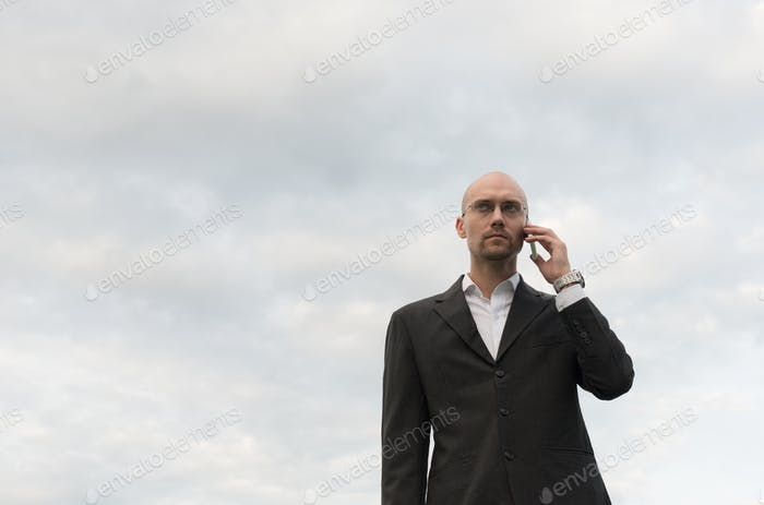 Handsome bald businessman with beard stubble against view of the sky