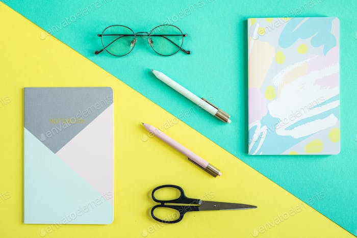 Two copybooks, pens, scissors and eyeglasses over blue and yellow backgrounds