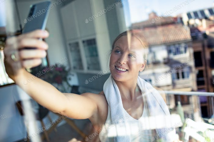 Sporty young woman taking a selfie with her smart phone while taking a break of exercise at home.