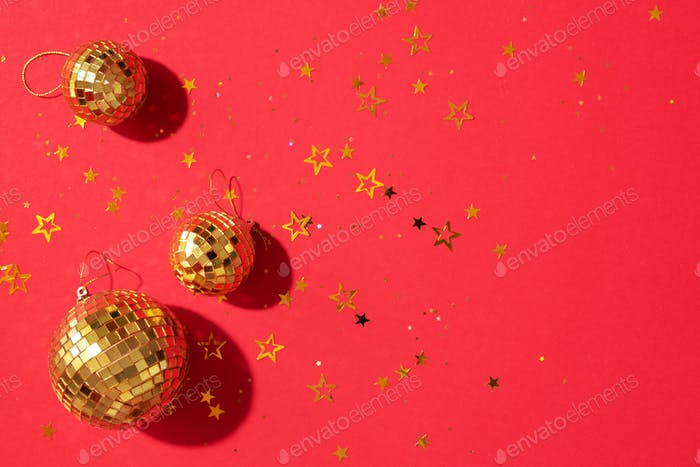Creative Christmas concept. Shiny gold disco balls over red background. Flat lay, top view. New year