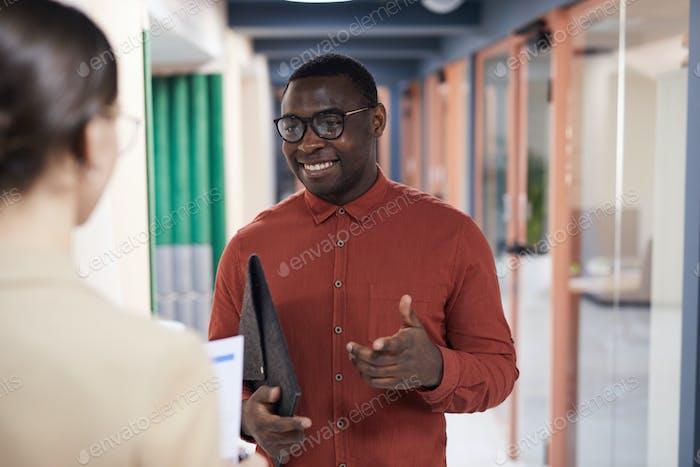 Fröhlicher afrikanischer Geschäftsmann im Gespräch mit Kollegen im Amt
