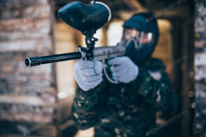 Paintball player with marker gun, front view