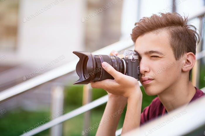 Teenager-Junge Fotos iert im Freien.