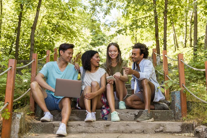 Multiethnic friends students outdoors using mobile phone and laptop