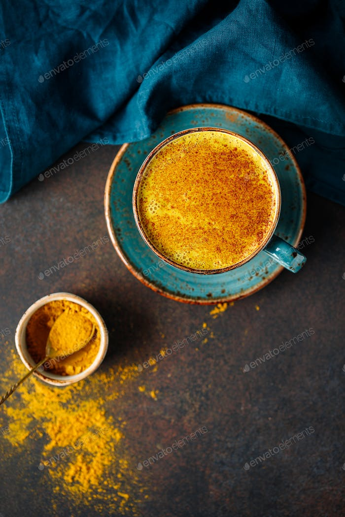 Top down view of turmeric latte cup on a textured dark background.