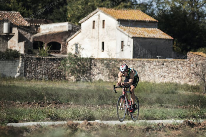 Man riding a bike in a country road with farmhouses around