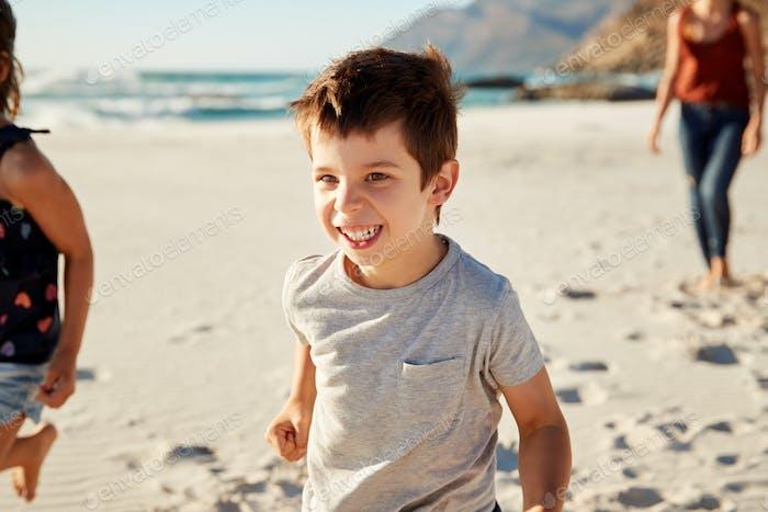Niño blanco de cuatro Año de edad de vacaciones con su familia corriendo en la Playa, de cerca