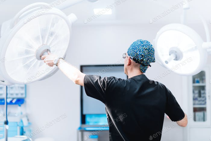 Male surgeon getting ready for surgery, fixing lamps and adjusting light in operation room