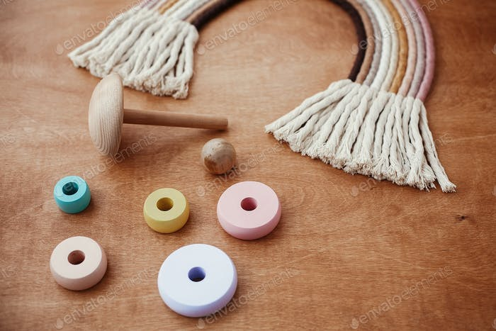 Modern colorful wooden pyramid with disassemble rings and macrame rainbow