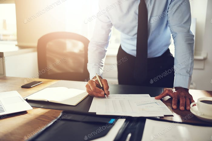 Businessman leaning on his office desk signing financial documents