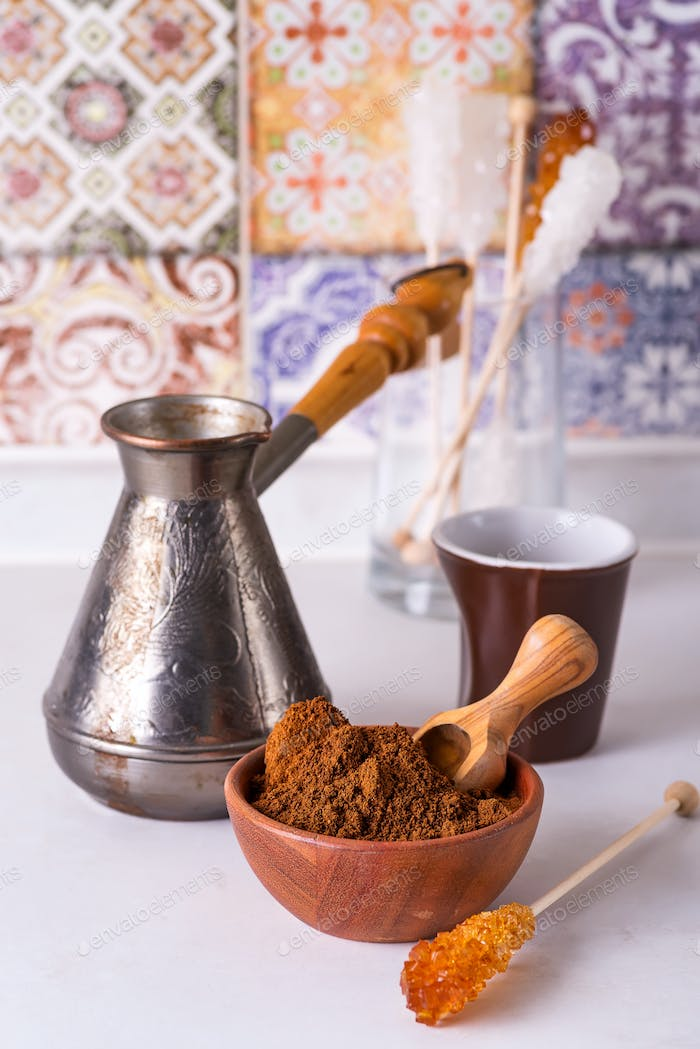 Grinded coffee in a wooden bowl with brown sugar stick on the background of a copper turks