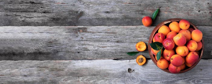 Ripe apricots with leaves on wooden background. Top view, copy space. Fruit banner. Healthy