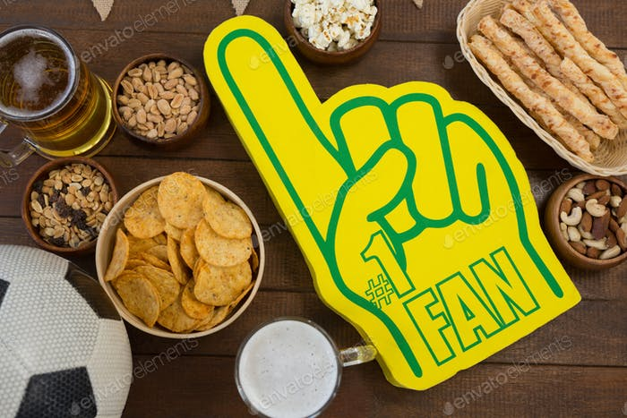 Foam hand, snacks and football on wooden table