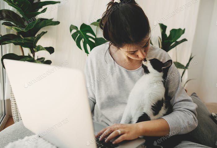 Young woman giving kiss to her cat and working on laptop