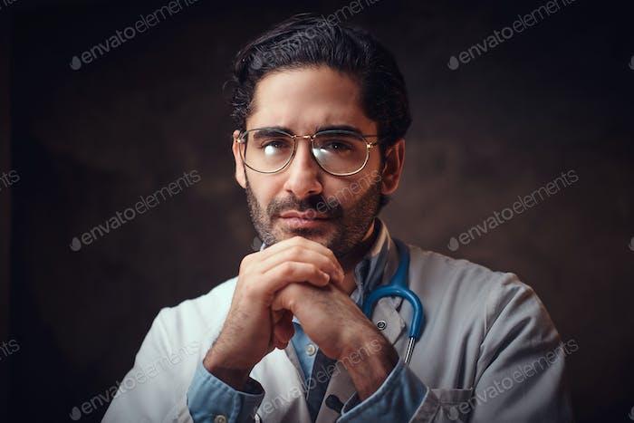 Porträt von intelligenten gutaussehenden Arzt über dunklen Hintergrund.