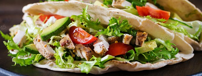 Pita bread sandwiches with grilled chicken meat, avocado, tomato