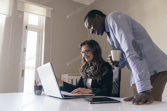 Молодая многоэтническая пара работает.