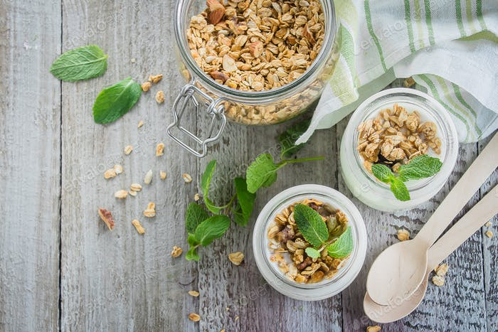 Healthy breakfast. Homemade oat granola with greek yogurt and mint leaves on wooden background.