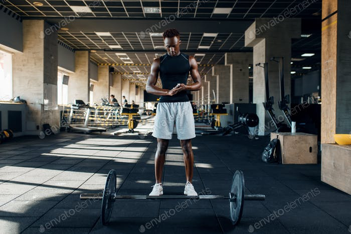 Athlete prepares for exercise with barbell in gym