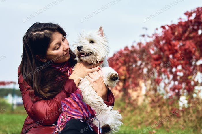 A lovely west highland white terrier with owner. Girl with her favorite dog