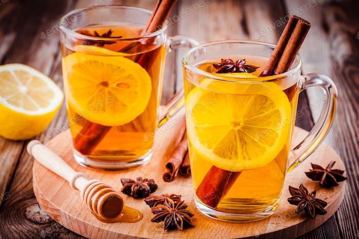 heißer Tee mit Zitrone, Anis und Zimt in Glasbecher