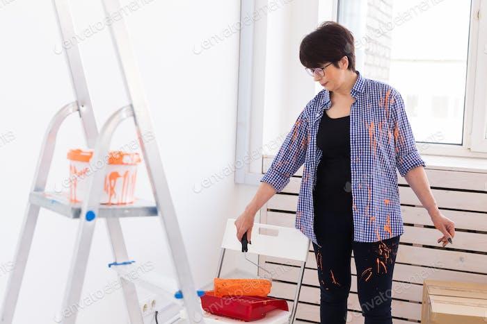 Ремонт в квартире. Счастливая женщина средних лет рисует стену краской